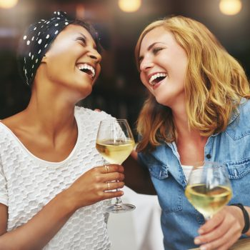 Two women laughing and holding glasses of white wine.