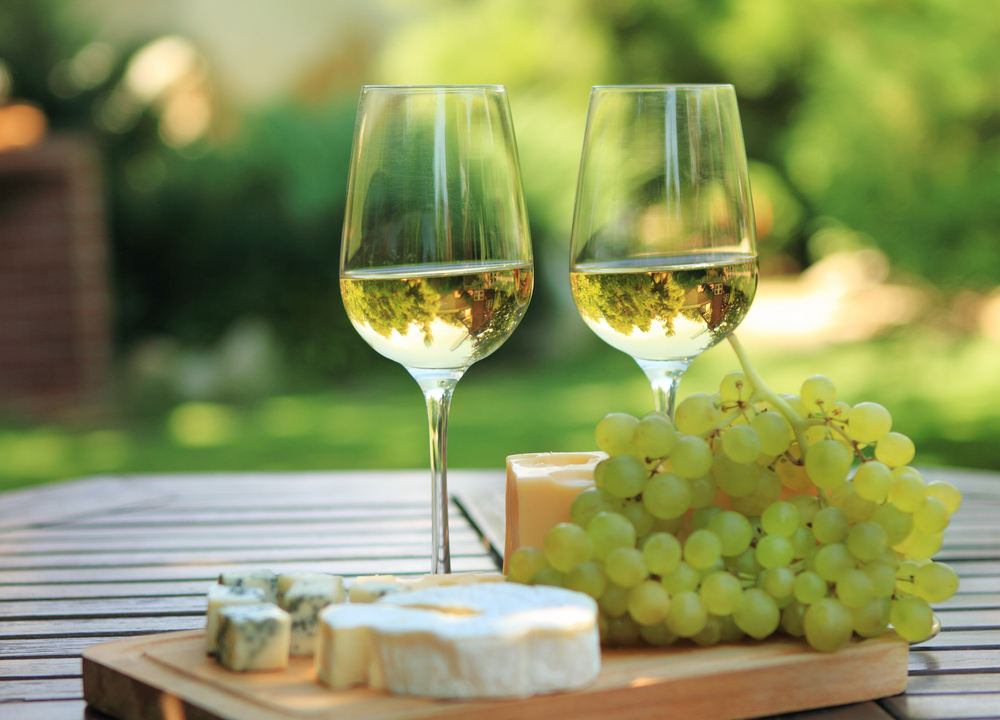 Two glasss of white wine sitting on a table with cheese and grapes.