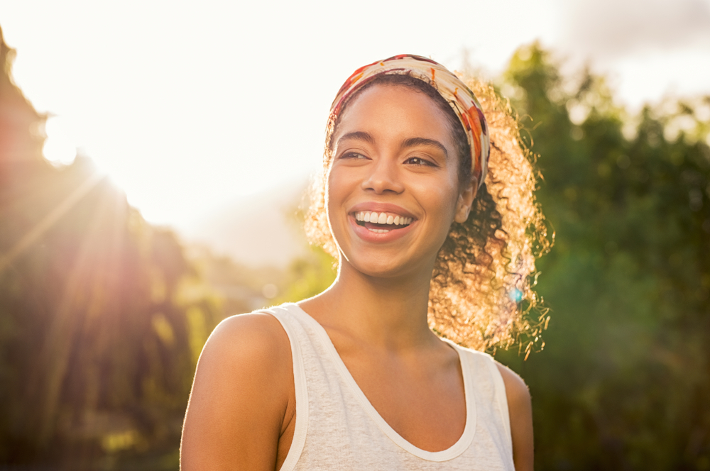 A woman smiling with the sun shining behind her