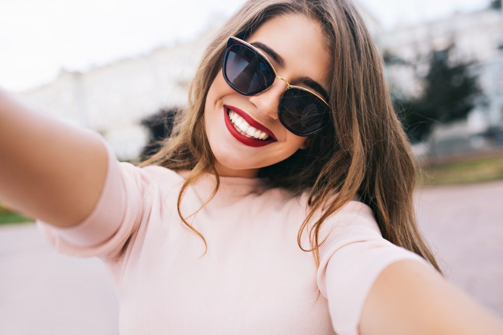 woman wearing sunglasses smiling and taking a selfie
