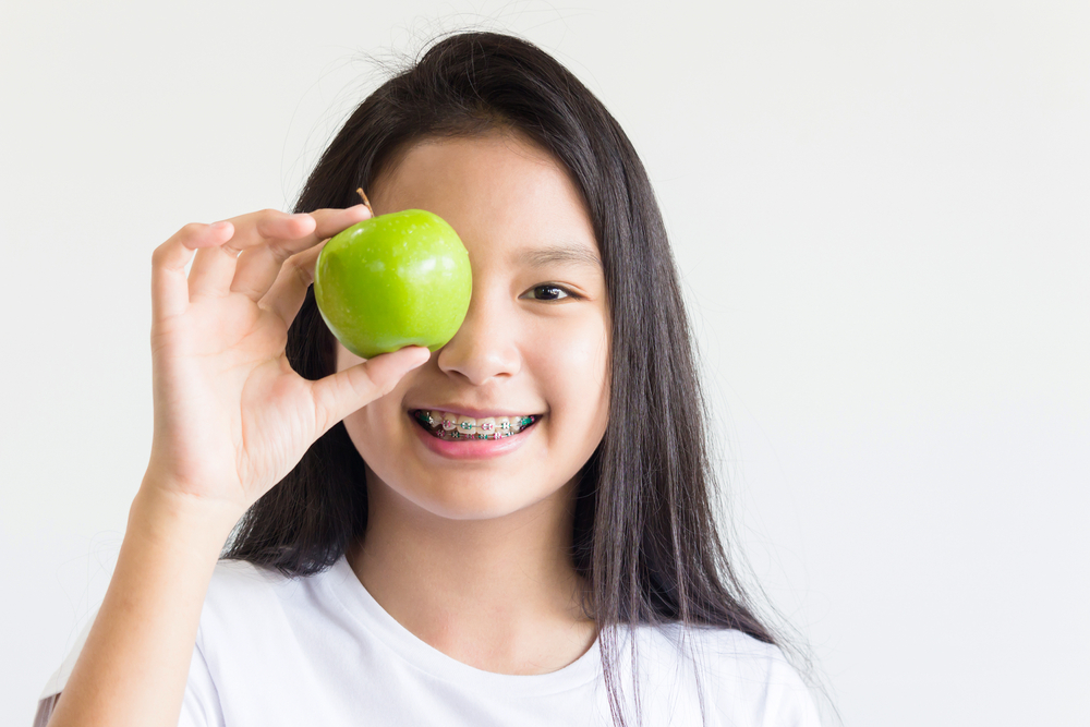 girl with braces holding an apple over her eye