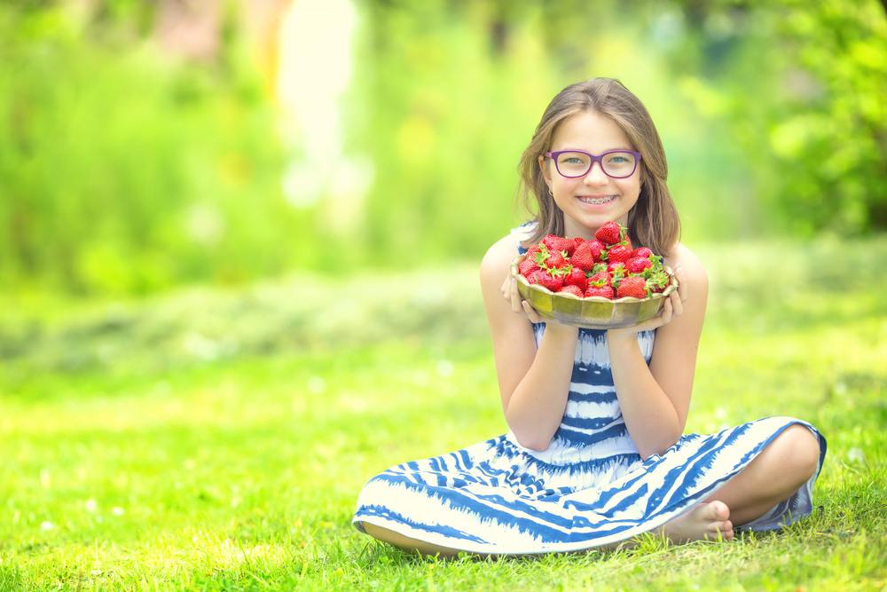 little girl with braces holding a bowl of strawberries