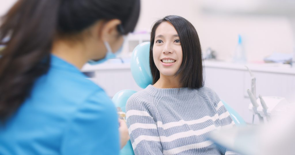 woman sitting in dentist chair being treated by a professional