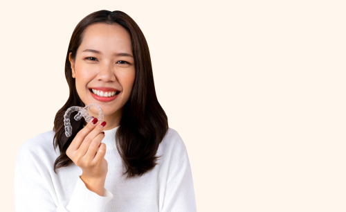 young asian woman wearing a white blouse holding her aligners up and smiling