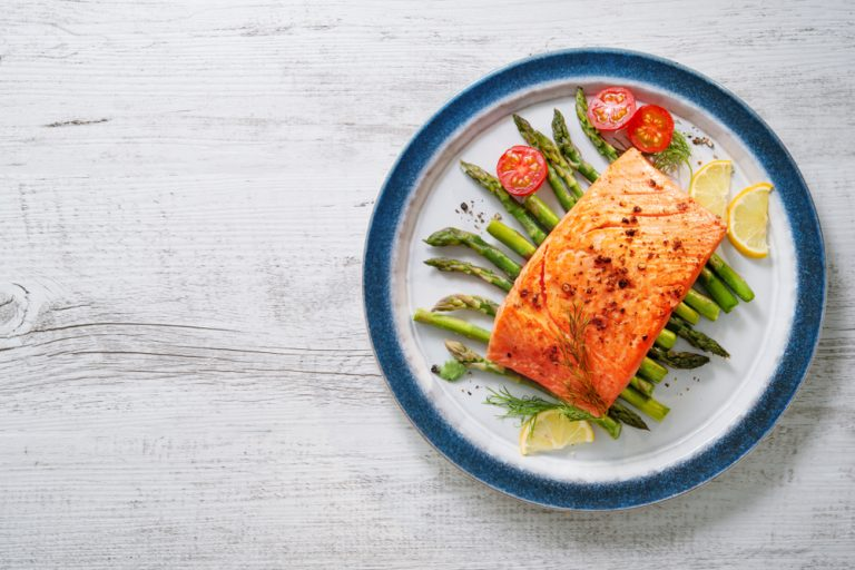 salmon sitting on top of asparagus on a plate from a bird's eye view